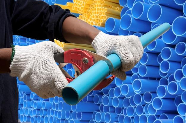Trabalhador cortando tubos de pvc em canteiro de obras