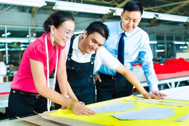 Trabalhador, costureira e ceo em uma fábrica