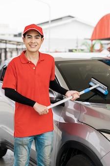 Trabalhador da bomba lavando janela do carro no posto de gasolina