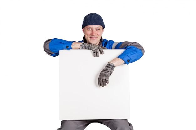 Trabalhador da construção civil amigável segurando um cartaz em branco, branco. isolado no branco