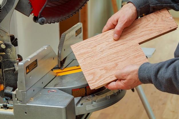 Trabalhador da construção civil, aparando parquet em usando corte de serra de esquadria circular