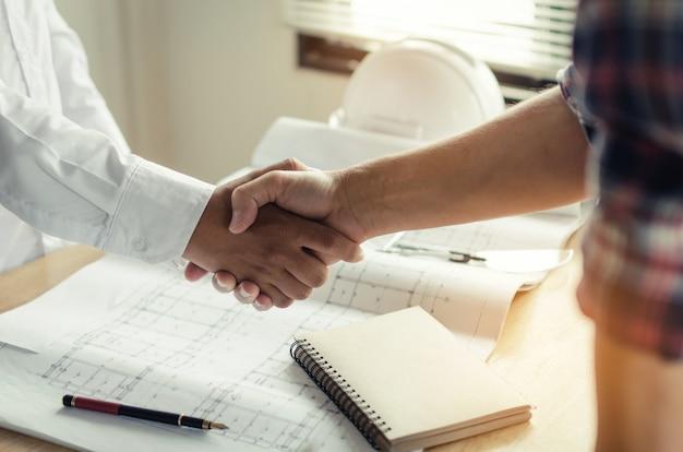 Trabalhador da construção civil apertando as mãos com o cliente