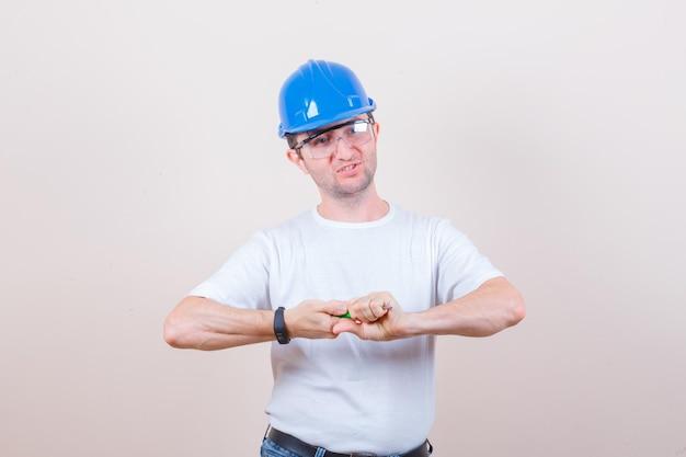 Trabalhador da construção civil apertando uma chave de fenda em uma camiseta, jeans, capacete