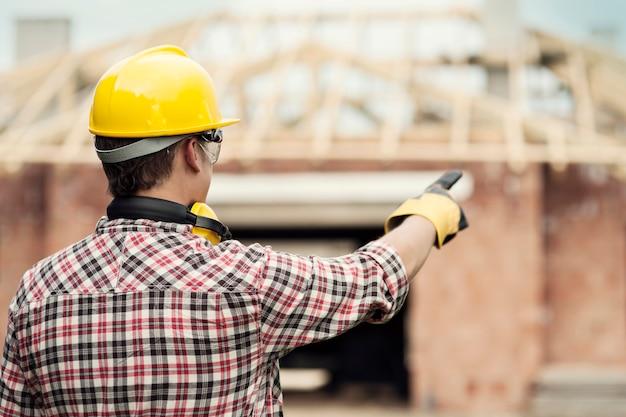 Trabalhador da construção civil apontando para algo