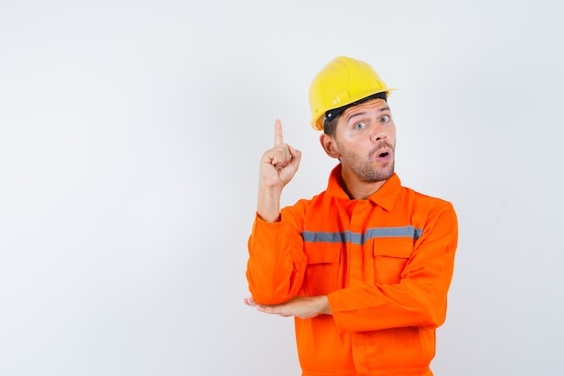 Trabalhador da construção civil apontando para cima em uniforme, capacete e olhando surpreso, vista frontal.