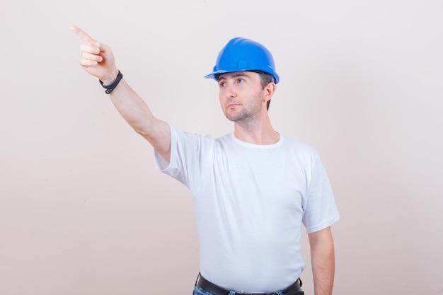 Trabalhador da construção civil apontando para longe em camiseta, jeans, capacete e parecendo focado