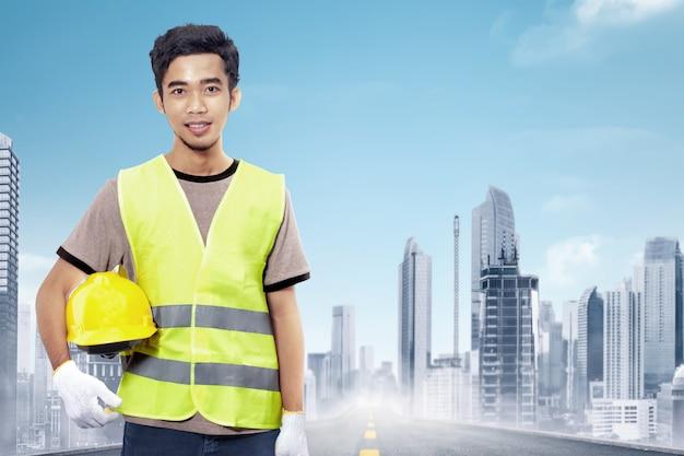 Trabalhador da construção civil asiática atraente segurando o capacete amarelo