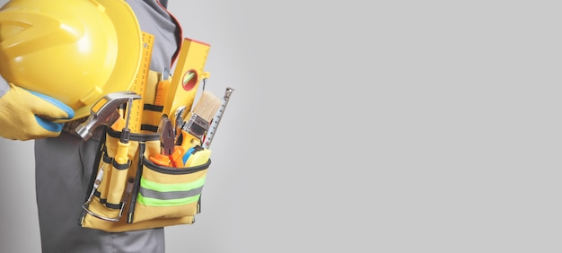Trabalhador da construção civil caucasiano com um cinto de ferramentas ferramentas de construção