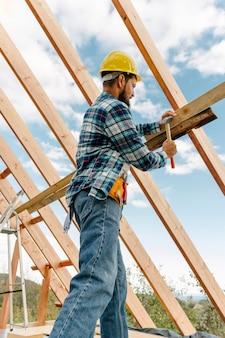Trabalhador da construção civil com capacete construindo o telhado da casa