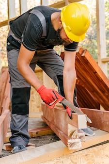 Trabalhador da construção civil com capacete cortando pedaço de madeira com serra