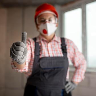 Trabalhador da construção civil com capacete e máscara facial aparecendo os polegares
