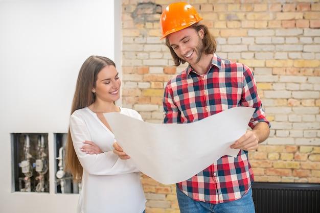 Trabalhador da construção civil com capacete laranja e um cliente discutindo o design do projeto