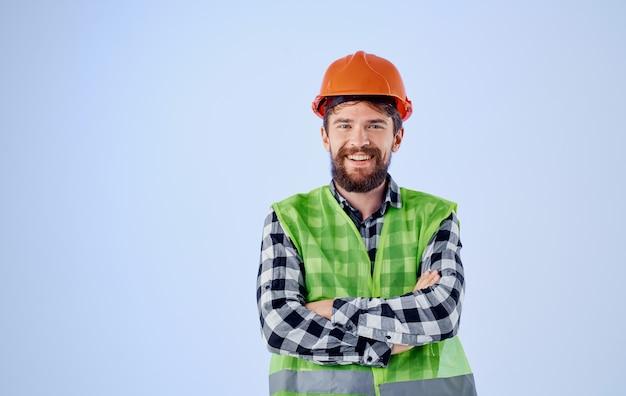 Trabalhador da construção civil com capacete laranja na parede azul e colete reflexivo de camisa xadrez