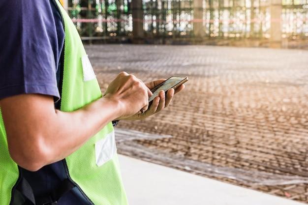 Trabalhador da construção civil com capacete verde trabalhando no canteiro de obras usando o smartphone