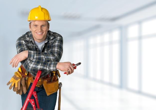 Trabalhador da construção civil com ferramentas em um prédio vazio