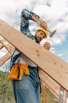 Trabalhador da construção civil com martelo construindo o telhado da casa