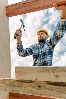 Trabalhador da construção civil com martelo e capacete construindo o telhado da casa