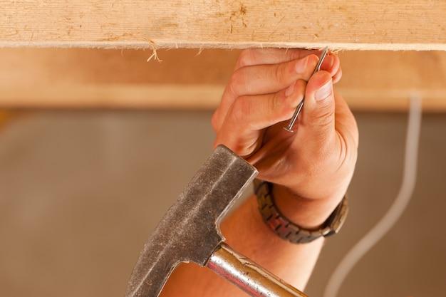Trabalhador da construção civil com martelo e prego