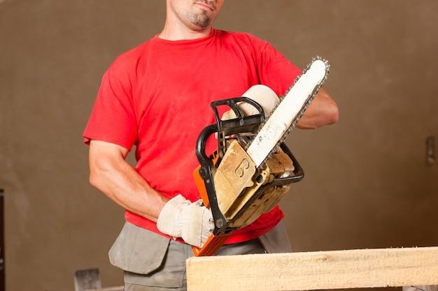 Trabalhador da construção civil com motosserra