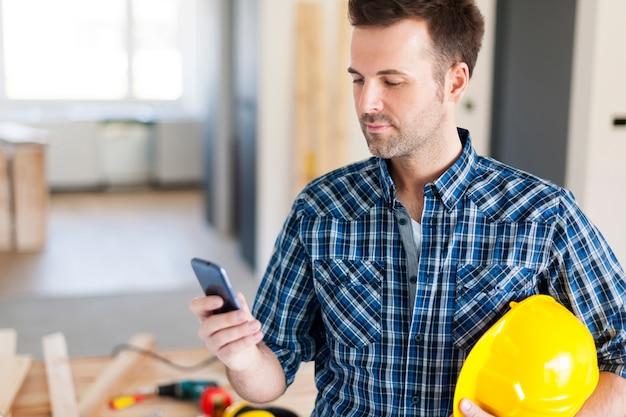 Trabalhador da construção civil com telefone celular contemporâneo