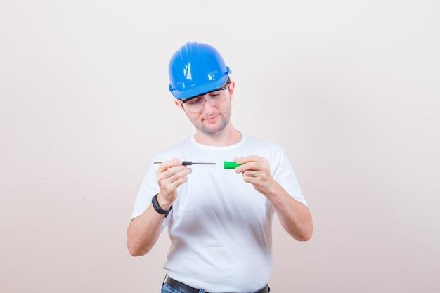 Trabalhador da construção civil consertando uma chave de fenda em uma camiseta, jeans, capacete e olhando com cuidado