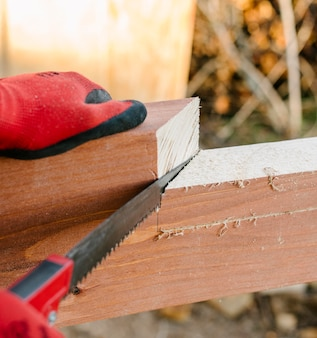 Trabalhador da construção civil cortando pedaço de madeira com serra
