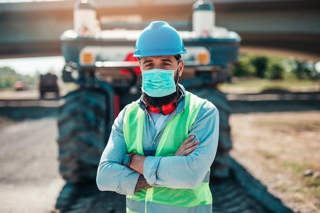 Trabalhador da construção civil de estradas do sexo masculino jovem com máscara protetora facial em seu trabalho. dia de sol brilhante. luz forte.