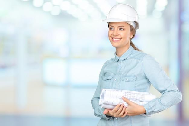 Trabalhador da construção civil de mulher ou arquiteto em um capacete de segurança segurando papéis