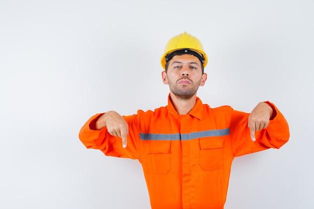 Trabalhador da construção civil de uniforme, capacete apontando para baixo e olhando confiante, vista frontal.