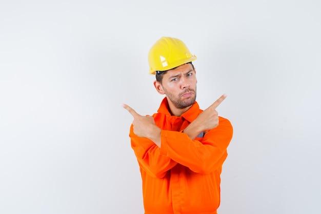 Trabalhador da construção civil de uniforme, capacete apontando para longe e olhando confiante, vista frontal.