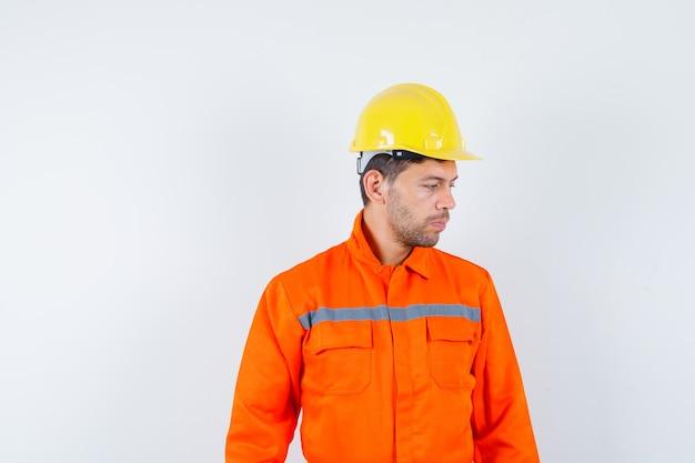 Trabalhador da construção civil de uniforme, capacete olhando para baixo e olhando pensativo, vista frontal.
