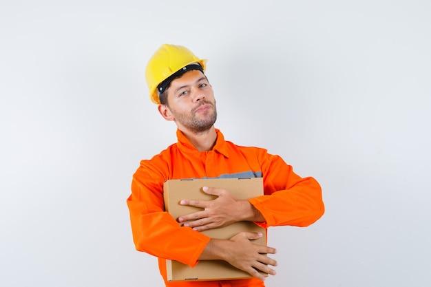 Trabalhador da construção civil de uniforme, capacete segurando uma caixa de papelão e olhando positiva, vista frontal.