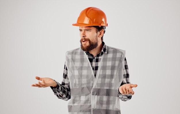 Trabalhador da construção civil de uniforme e capacete laranja