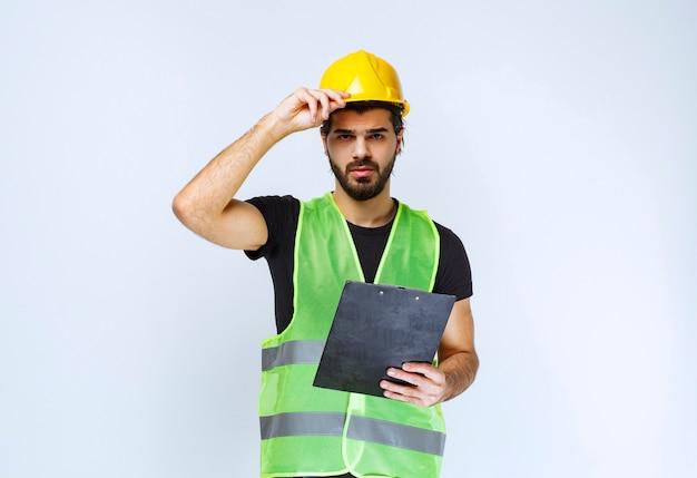 Trabalhador da construção civil de uniforme segurando um plano de projeto.