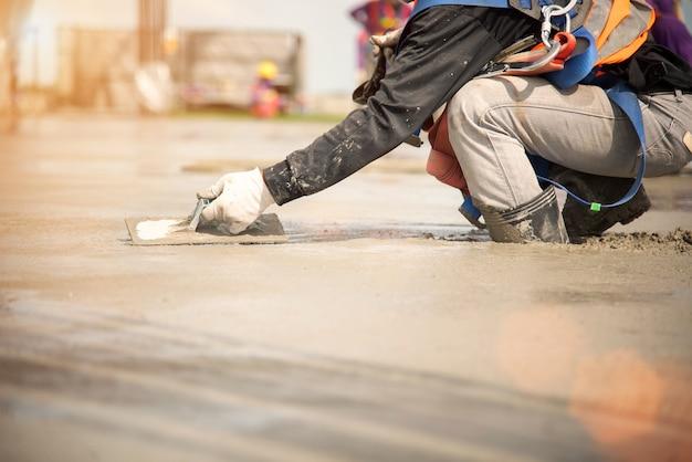 Trabalhador da construção civil despejando concreto