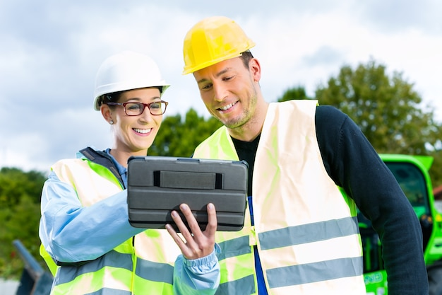 Trabalhador da construção civil e engenheiro no local discutindo plantas no bloco ou tablet, escavadeira e outras máquinas de construção Foto Premium