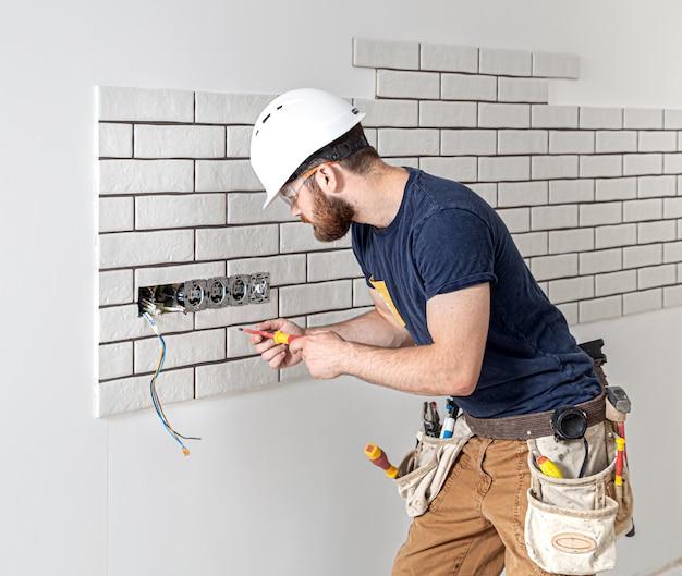Trabalhador da construção civil eletricista com barba de macacão durante a instalação de tomadas. conceito de renovação em casa.
