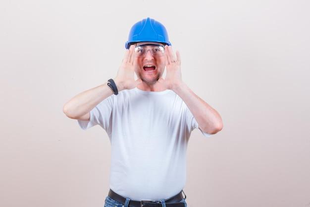 Trabalhador da construção civil em camiseta, jeans, capacete gritando ou anunciando algo