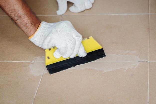 Trabalhador da construção civil em luvas brancas está trabalhando para rejuntar os azulejos do banheiro.
