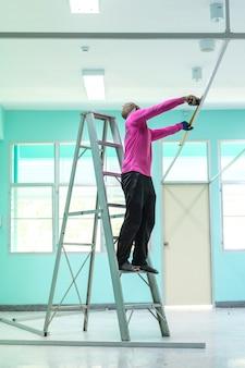 Trabalhador da construção civil em pé na escada de alumínio ou escada usando uma fita métrica.