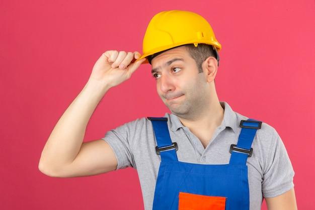 Trabalhador da construção civil em uniforme e capacete de segurança com rosto infeliz tocando seu capacete de segurança amarelo isolado na rosa