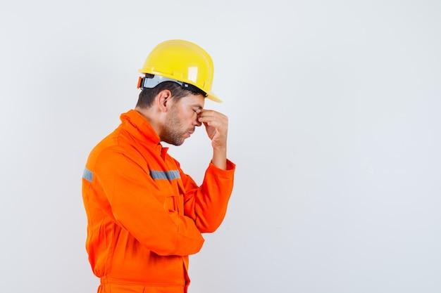 Trabalhador da construção civil esfregando os olhos e o nariz de uniforme, capacete e parecendo cansado.