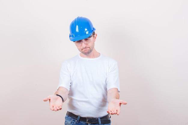 Trabalhador da construção civil esticando as mãos em gesto de dar ou receber em camiseta, jeans, capacete e parecendo chateado