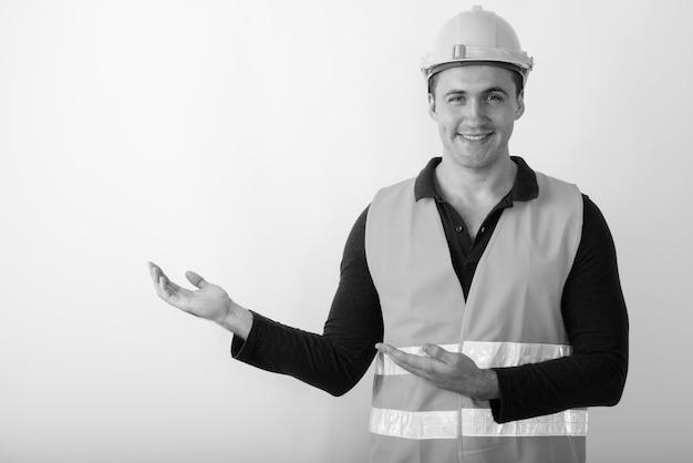 Trabalhador da construção civil feliz jovem homem musculoso sorrindo ao mostrar algo.
