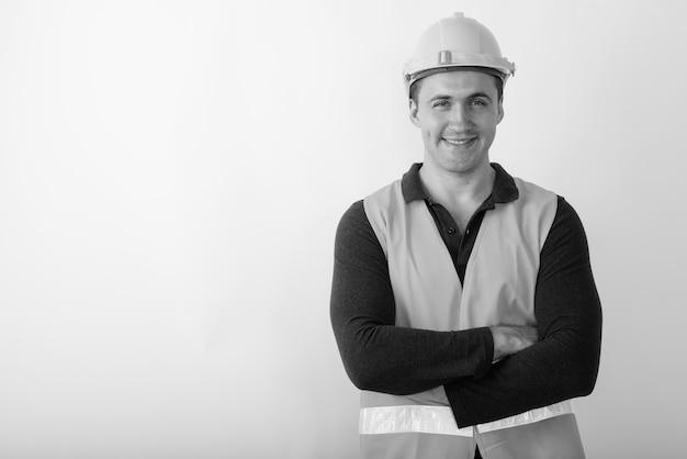 Trabalhador da construção civil feliz jovem homem musculoso sorrindo com os braços cruzados.