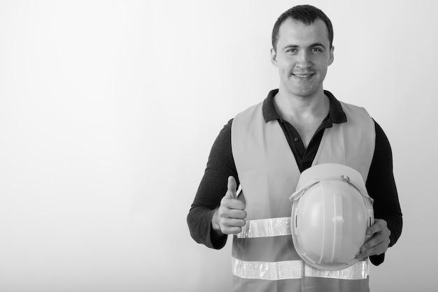 Trabalhador da construção civil feliz jovem homem musculoso sorrindo enquanto abre o polegar e segura o capacete