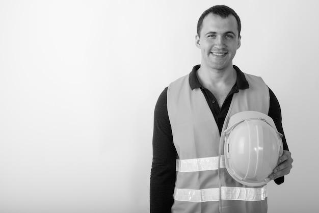 Trabalhador da construção civil feliz jovem homem musculoso sorrindo enquanto segura o capacete.