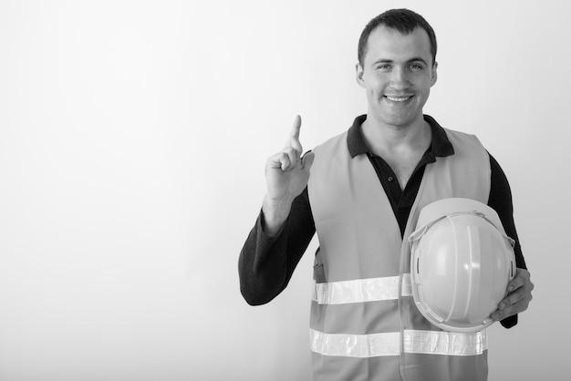 Trabalhador da construção civil feliz jovem homem musculoso sorrindo, segurando o capacete e apontando para cima