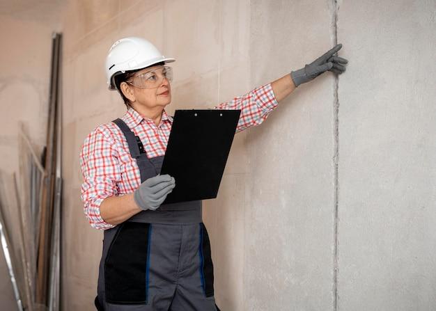 Trabalhador da construção civil feminino com capacete inspecionando com prancheta