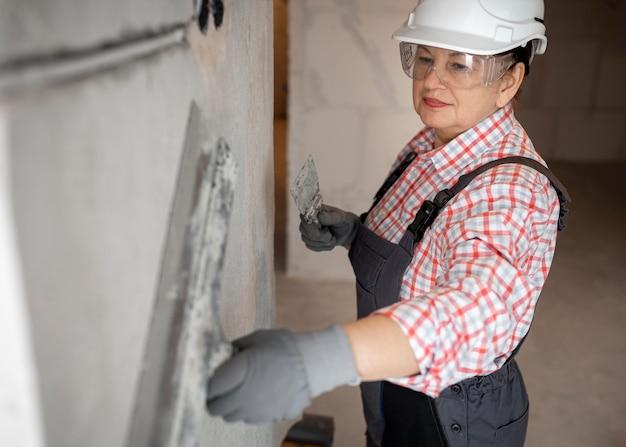 Trabalhador da construção civil feminino com capacete trabalhando na parede